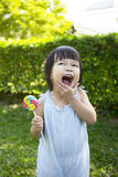 Portrait of a little girl with lollipop. In the park Royalty Free Stock Photo