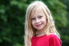 Portrait little girl with long blond hair in a red sweater smiling and looking directly at the camera royalty free stock photography