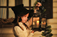 Portrait of a little girl looking at the candle in the lantern Stock Images
