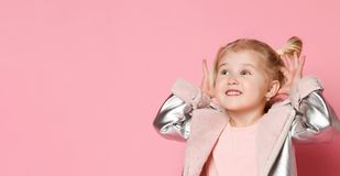 Portrait of a little girl looking to the side of the frame and showing teasers on a pink background royalty free stock image