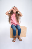 Portrait of a little girl looking up through fingers. Portrait of a little girl sitting on wooden box and looking up through fingers isolated on a white Stock Image