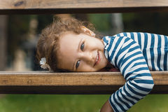 Portrait of little girl lying on bench in a park, Royalty Free Stock Photo