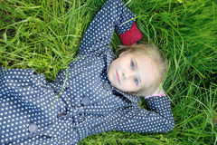Portrait of little girl lying on green grass. And dreaming Stock Image