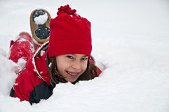 Portrait of little girl lying on the ground buried by snow Royalty Free Stock Photos