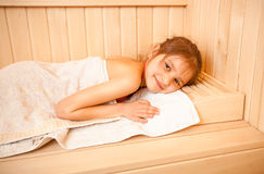 Portrait of little girl lying on towel at sauna Stock Photography