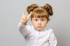 Portrait of little girl making rock and roll sign. Isolated royalty free stock image