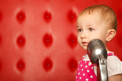 Portrait of little girl with microphone on red Stock Images