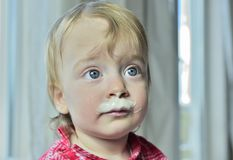 Portrait of a little girl with milk moustaches. Royalty Free Stock Image