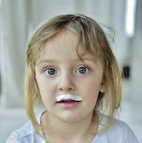 Portrait of a little girl with milk moustaches. Stock Images