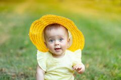 Portrait of a little girl 8 months old sitting in the summer on the green grass in a yellow summer dress and hat and laughing