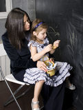 Portrait of little girl with mother at blackboard, making lessons Royalty Free Stock Images
