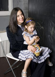 Portrait of little girl with mother at blackboard, making lessons Stock Image