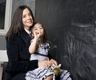 Portrait of little girl with mother at blackboard, making lessons Stock Photos