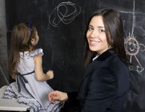 Portrait of little girl with mother at blackboard, making lessons Royalty Free Stock Photos