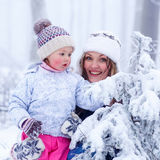 Portrait of a little girl and mother in winter hat in snow fores Stock Photo