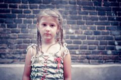 Portrait of a little girl near a brick wall. Stock Image
