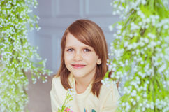 Portrait of a little girl near a flowers in a studio. Portrait of a pretty little girl near a flowers in a studio Royalty Free Stock Images