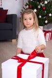 Portrait of little girl opening big gift box near Christmas tree Stock Photography
