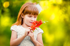 Portrait of a little girl outdoor in a garden smelling the flowe Stock Image