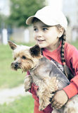 Portrait of little girl outdoors with a dog. In her arms Royalty Free Stock Images