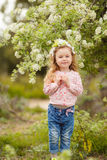 Portrait of little girl outdoors in a lush garden. Stock Image