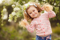 Portrait of little girl outdoors in a lush garden. Stock Photography