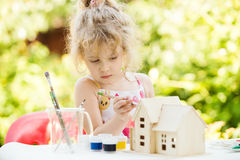 Portrait of little girl paints wooden model of house Royalty Free Stock Images