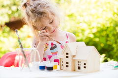 Portrait of little girl paints wooden model of house Stock Images