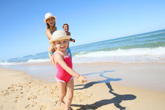Portrait of little girl and parents running on sandy beach Stock Photography