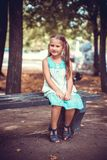 Portrait of a little girl in the park on a bench Royalty Free Stock Photos