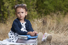 Portrait of little girl in park playing with her laptop Stock Image