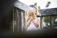 Portrait of a little girl in the park. Little girl is sucking her thumb while in park Stock Image