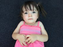 Portrait of a little girl with pigtails in pink dress lying on b Royalty Free Stock Photos