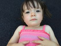 Portrait of a little girl in pink dress lying on black floor Stock Photos