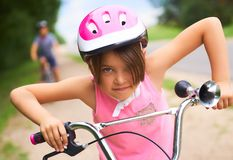 Portrait of a little girl in a pink safety helmet driving her bike. Safe movement of bicycles on the roads royalty free stock images