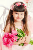 Portrait of a little girl, pink tulips in hands Stock Images