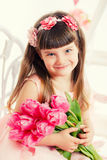 Portrait of a little girl, pink tulips in hands Stock Image