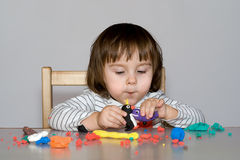 Portrait little girl is playing with coloful dough Royalty Free Stock Photos