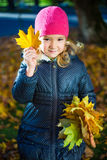 Portrait of little girl playing with maple leaves in autumn park Stock Photos