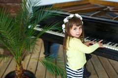 Portrait of a little girl playing a piano. Portrait of a little girl playing a black piano Stock Photo
