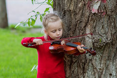 Portrait of a little girl playing the violin in a park on a summer day. Girl playing the violin in a bright sunny day outdoors Stock Photo