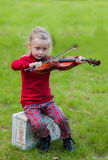 Portrait of a little girl playing the violin in a park on a summer day. Girl playing the violin in a bright sunny day outdoors Stock Images
