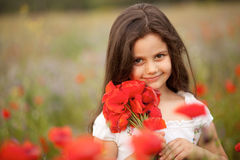Portrait of a little girl with poppies. Portrait of a little smiling brunette beautiful girl wearing white dress and holding red poppies flowers stock image