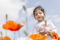 Portrait of a little girl on poppy flowers field in front of cloudy sky royalty free stock images