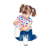 Portrait of a little girl pouring milk in glass Royalty Free Stock Images
