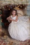 Portrait of a little girl princess in a crown in a white dress stock images