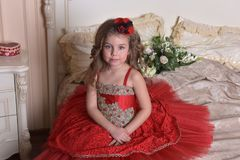 Portrait of a little girl princess in a red dress and hat sitting stock image