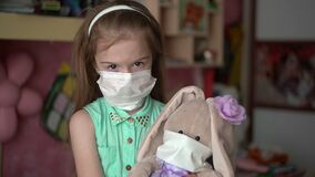 Portrait little girl with a rabbit toy in disposable face masks under quarantine for self-isolation. Pandemic epidemic