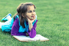 Portrait of little girl reading a book Stock Images