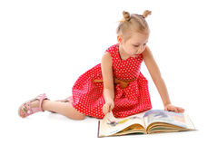 Portrait of a little girl reading books, sitting on the floor stock photography